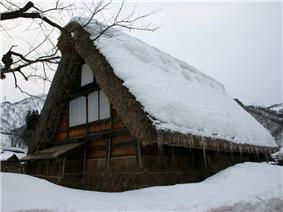 A thatched wooden house with very steep gable covered by snow.