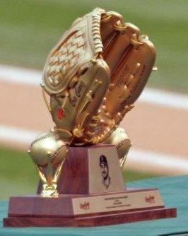 A trophy sits on a green table topped by a golden baseball glove flanked by two golden baseballs.