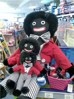 A rag doll, his face a caricature of a black person, in a toy store, holding copies of himself in his lap and more copies in a basket.