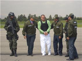 A handcuffed man in a light green T-shirt, flak jacket and white pants being escorted by two men on either side in green jackets and caps with the Spanish word