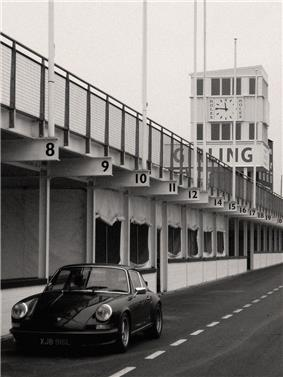 Black and white picture showing dark colours car in a pits area.