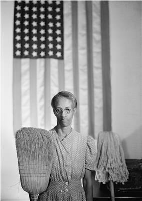 Man holding up a broom and mop with an American flag hanging in the background, in imitation of the original American gothic.