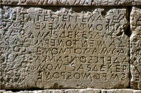 Stone wall with inscription in Greek letters.