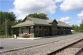 Image of a train depot that looks old but has been restored, with train tracks in the foreground.
