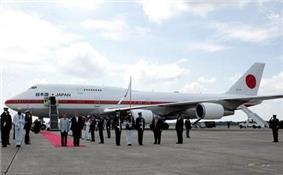 Parked VIP aircraft with red carpet and assembled entourage.