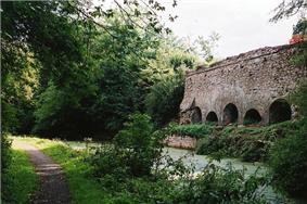 A footpath to the left, water in the centre of the picture and on the right a stone wall with arch shaped openings.