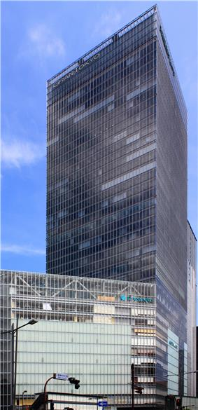Ground-level view of a glass, rectangular high-rise