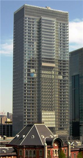 Mid-level view of a rectangular, glass high-rise; one side is vertically bisected by a section