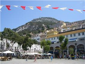 A broad, tree-lined sguare with shops and cafes on the perimeter and tiers of buildings on a slope leading up to the Rock of Gibraltar in the background