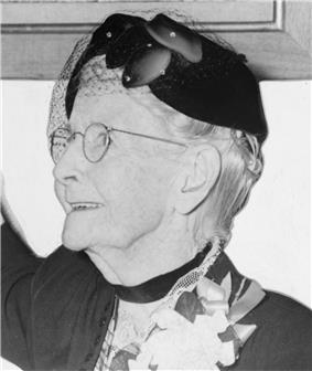 Grandma Moses, wearing eyeglasses and a fancy hat