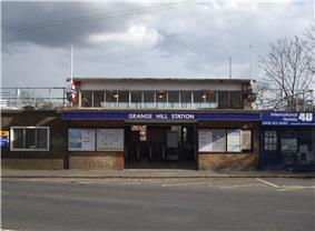 A brown-bricked building with a blue sign reading