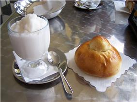 A frozen white dessert in a clear glass, next to a piece of bread