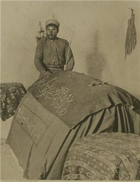 A sepia-toned photograph showing a man wearing a turban, his left arm cradling a thin staff, and standing behind and with his right hand upon a centotaph draped with fabric on which is an inscription in Arabic script