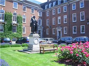 A grassy area with floral shrubs and a central statue on a plinth, with terraced buildings in the background