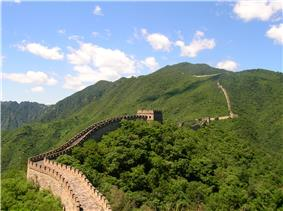 A high defensive wall with watch towers running through a mountain landscape.