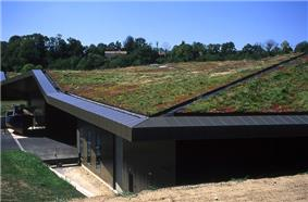 A low building has a roof completely covered with soil and grass. It appears to be built into a hillside