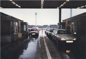 View of two lines of vehicles passing between two buildings, with four passport control booths visible, under a corrugated metal roof. A long line of vehicles stretches into the distance below towers ringed with searchlights.