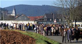 A large number of people of various ages standing and walking along a road in front of a high concrete wall, behind which houses and a church are visible in a wooded valley.