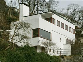 A small, flat-roofed, stucco house designed with simple, rectangular shapes, and built into a hillside. The casement, paned, and plate glass windows are wood framed.