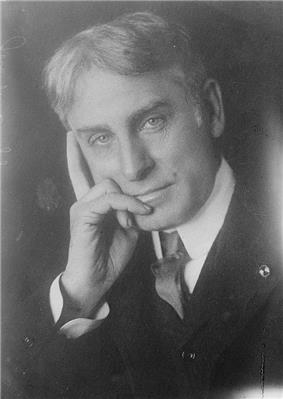 Middle-aged, thick-haired man wearing a suit and tie, gazing forward, his right hand touching the side of his face thoughtfully.