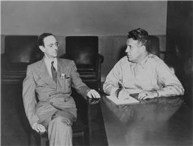 A large man in uniform and a bespectacled thin man in a suit and tie sit at a desk.