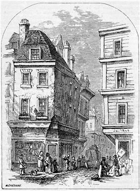 People congregate at the entrance to a narrow street, overlooked by two four-storey buildings.  Each floor of the right-most building projects further over the street than the floor below.  At the corner of each building, shops advertise their wares.  A cart is visible down the street, and one man appears to be carrying a large leg of meat.
