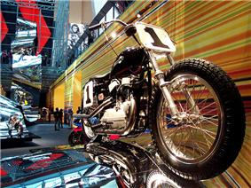 A pristine 1960s Harley-Davidson scrambler style motorcycle mounted as if riding over a rolling reflective steel surface.
