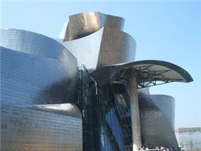 A building made of many curved, shiny metal surfaces, themselves composed of smaller plates. The door is under a curved metal roof supported by a pillar.