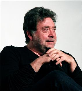 A photo of a bearded, black haired Mexican male with sitting with his hands clasped over his knee. He is wearing a black shirt and black pants.