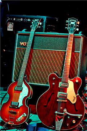 Two electric guitars displayed with an amplifier.