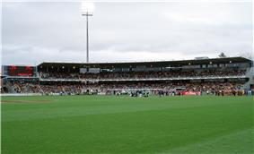A two tier stand and scoreboard filled with people in the backdrop of an oval grass playing surface.