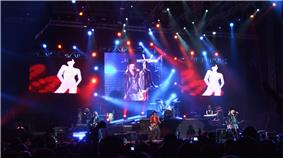 Six Members of a band are visible on stage. A singer with a black hat and leather jacket with torn jeans sings into a red microphone, his image is projected onto the large screen hanging from the venue. Red and blue spotlights beam around the stage, a darkened crow is in the forefront. Video screens to the left and right display animated dancers. A man in a red shirt is playing a white guitar center stage while two men in black shirts on keyboards flank him to either side of the stage. a drummer is at his kit on stage, risen above the rest of the stage.