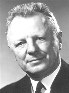Head and shoulder of a 60-ish man with a flattop haircut and in a coat and tie, looking directly at camera with head tilted to his right and a slight smile.