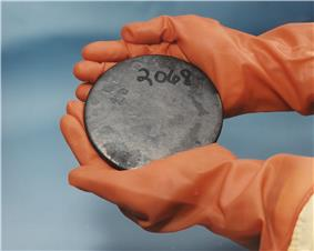Two hands in brown gloves holding a blotched gray disk with a number 2068 hand-written on it