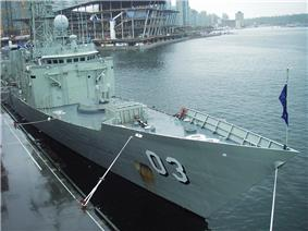 Photograph of a frigate's bow and the front of her superstructure. Two weapons systems can be seen on the forward deck.