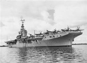 A aircraft carrier at anchor in still waters. Propeller aircraft are visible on her deck.