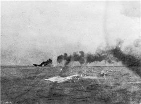 A large ship is sinking in the distance; a large dense cloud of smoke emanates from the wreck.