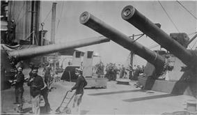The crowded midships area of HMSIndomitable dominated by the masses of the 12-inch guns of 'P' and 'Q' turrets, each of which is trained across the deck.