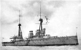 A large grey warship with two tripod masts and three funnels