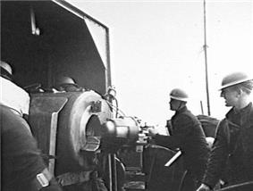 Gunners wearing steel helmets load a shell into a large calibre weapon