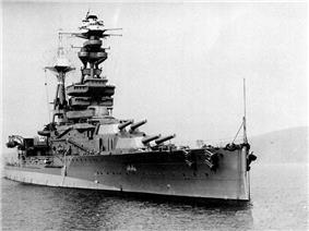A three-quarter view of a heavily-armoured battleship at anchor. There are two main turrets visible before the bridge, each housing a pair of 15-inch guns. 6-inch guns are housed in a row of individual sideways-facing sponsons. The flank of the ship has a conspicuous bulge at the waterline