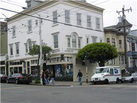A color photo of a building with 'Haight' and 'Ashbury' signs on opposite sides of its corner