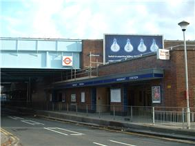 A red-bricked building with a blue sign reading