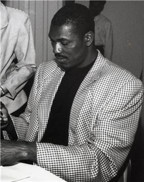 A man, wearing a checkered coat and a dark shirt, is signing an autograph.