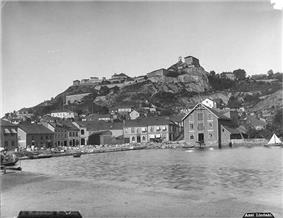 Modest buildings  along the water's edge are guarded by a fortress on the hill above.