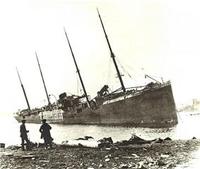 Two men observe a large beached ship with