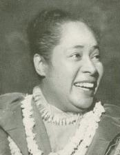 A smiling woman with a topknot and strings of shells around her neck
