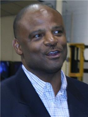 Head and shoulders of a bald black man wearing a light shirt and a black suit jacket.