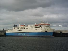 A large modern ferry with a blue hull and white topsides lies next to a harbour under grey skies.