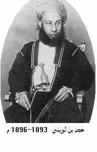 A black-and-white photograph of a man with a dark beard wearing a turban, a dark jacket, and a white shirt, sitting, and looking at the viewer
